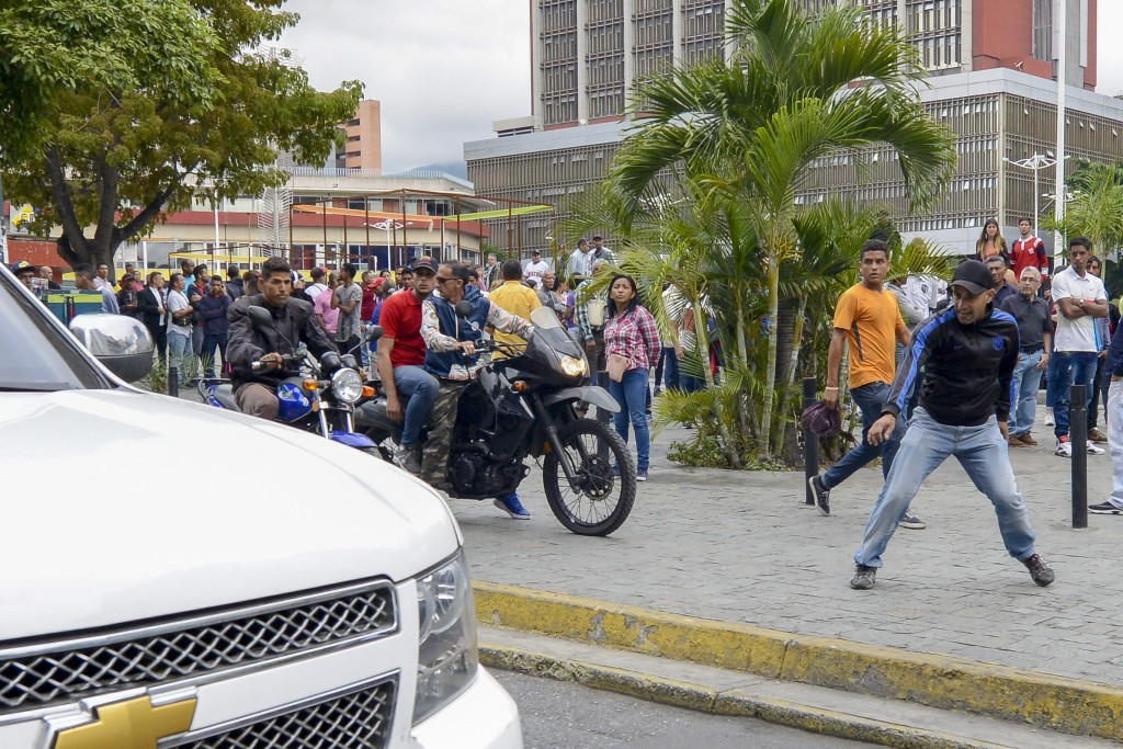 Government supporters hurl stones at a caravan of opposition lawmakers on their way to the National Assembly in Caracas, Venezuela, Wednesday, Jan. 15...