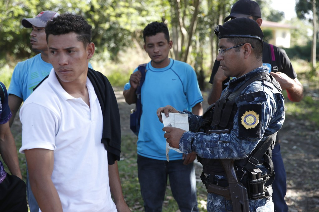 Honduras migrants trying to reach the United States show their ID card to a Guatemalan National Police agent after crossing the Honduran border, in Mo...