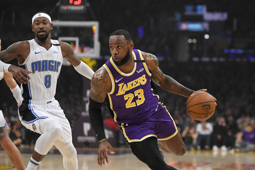 Los Angeles Lakers forward LeBron James, right, drives toward the basket as Orlando Magic guard Terrence Ross defends during the first half of an NBA ...