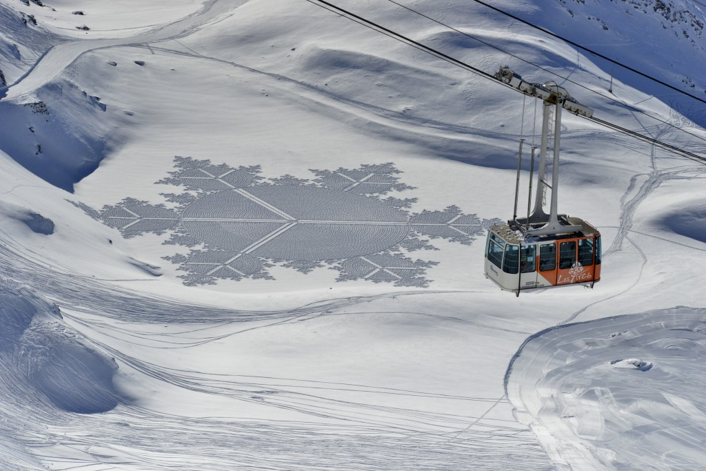 In this 2014 photo, provided by Simon Beck Snow Art, a gondola passes one of Beck's pieces in the snow at the Les Arcs ski resort in southeastern Fran...