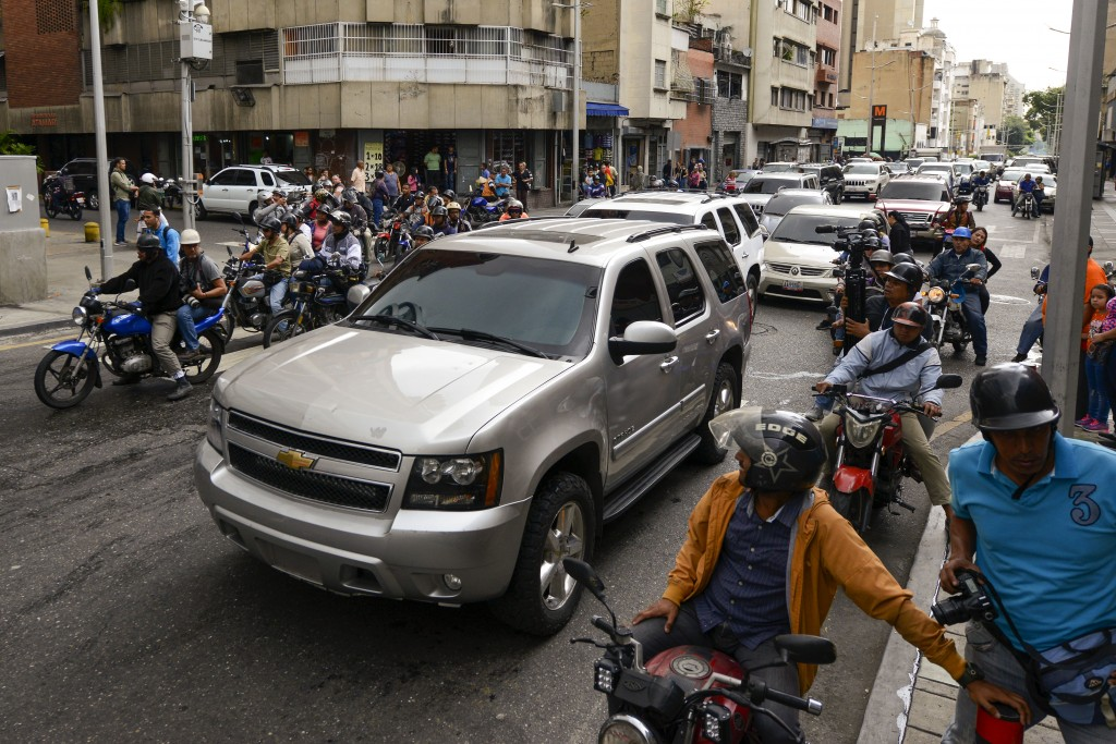 Journalists on motorbikes follow a caravan of opposition lawmakers on their way to the National Assembly in Caracas, Venezuela, Wednesday, Jan. 15, 20...