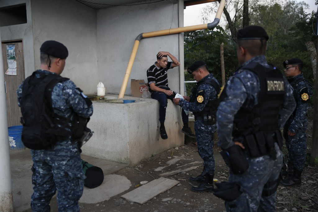 Guatemalan National Police agents checks documents of a Honduras migrant trying to reach the United States, at El Cinchado, Guatemala, in the border w...