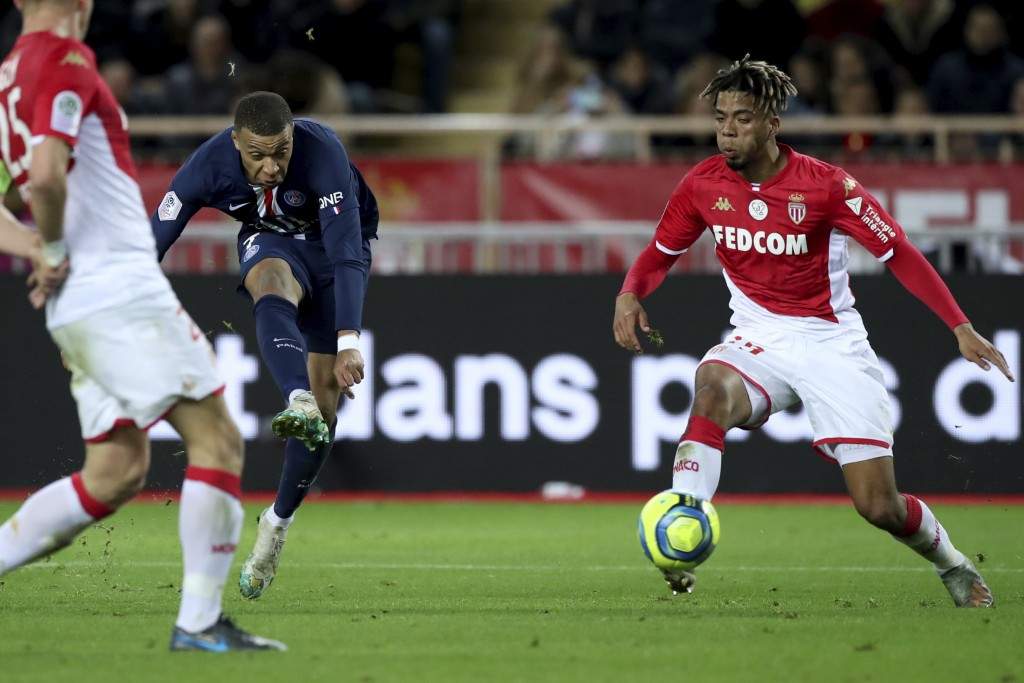 PSG's Kylian Mbappe, left, shoots during the French League One soccer match between Monaco and Paris Saint-Germain at the Louis II stadium in Monaco, ...