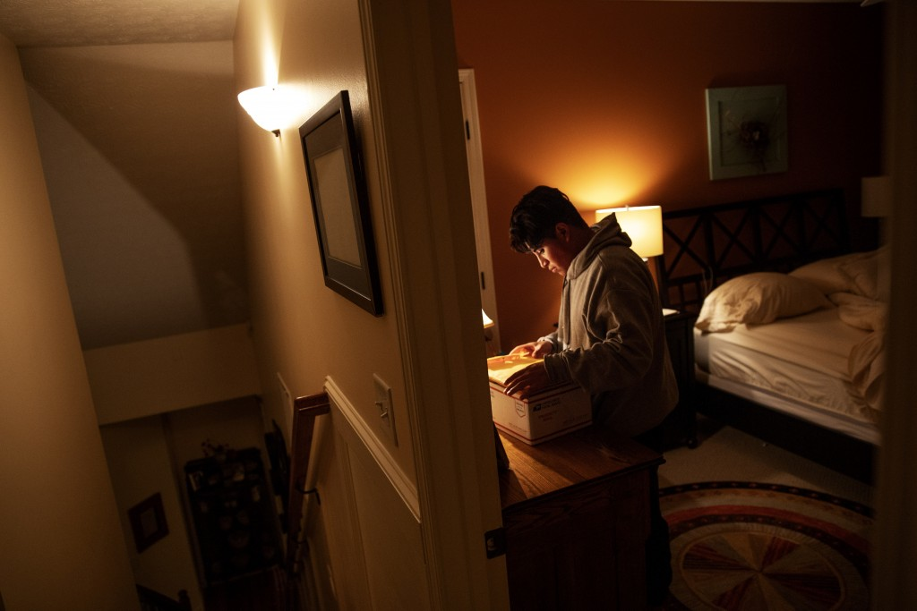 Andrea, 20, a transgender asylum seeker from Guatemala, sorts through documents as she settles in for the night at the home of a volunteer after her b...