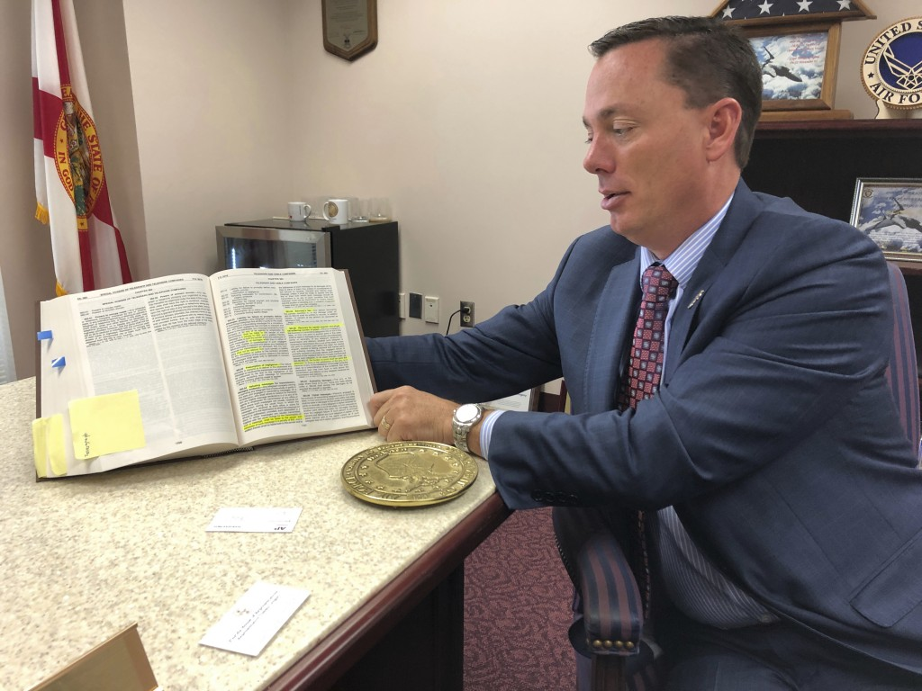 Rep. Tommy Gregory, holds a book of laws that includes antiquated statutes regulating the telegraph industry at his office Wednesday, Jan. 15, 2020, i...