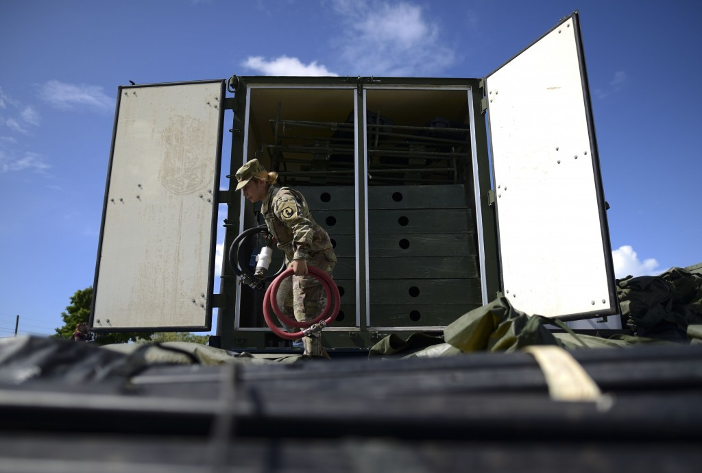 A member of the US army reserve works to set up up portable showers in a tent city for hundreds of people displaced by earthquakes in Guanica, Puerto ...