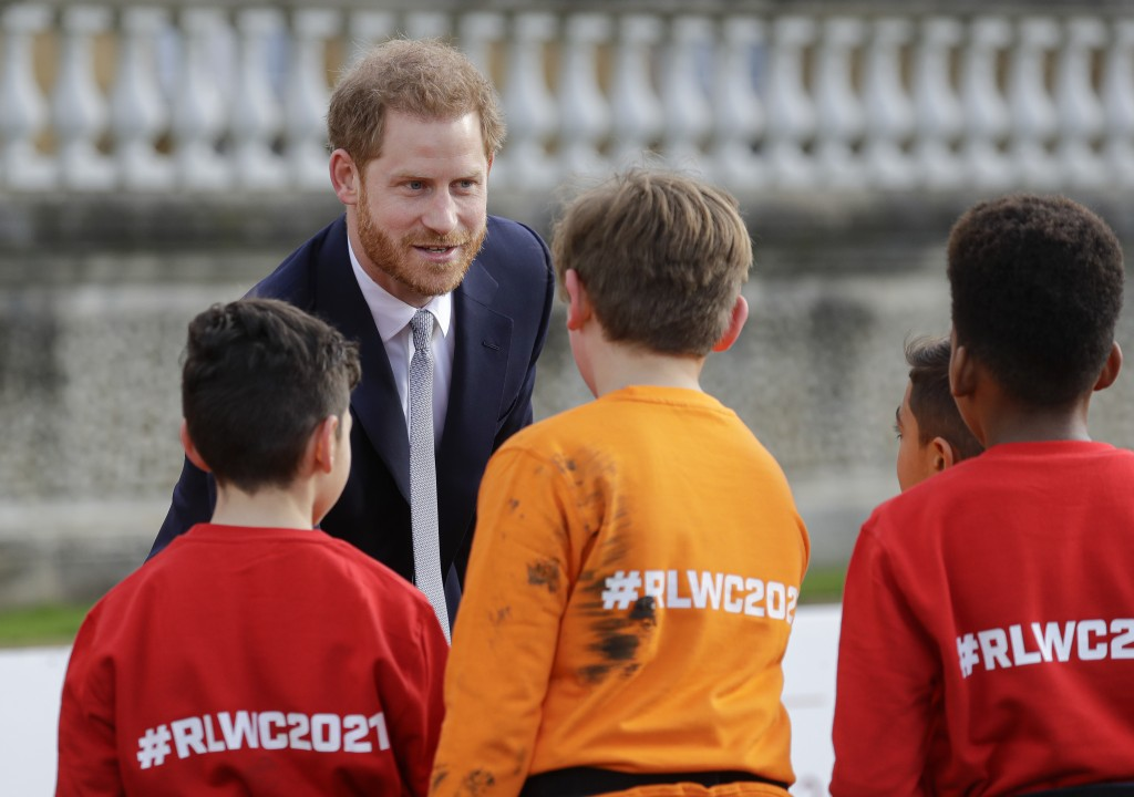 Britain's Prince Harry greets schoolchildren in the gardens at Buckingham Palace in London, Thursday, Jan. 16, 2020. Prince Harry, the Duke of Sussex ...