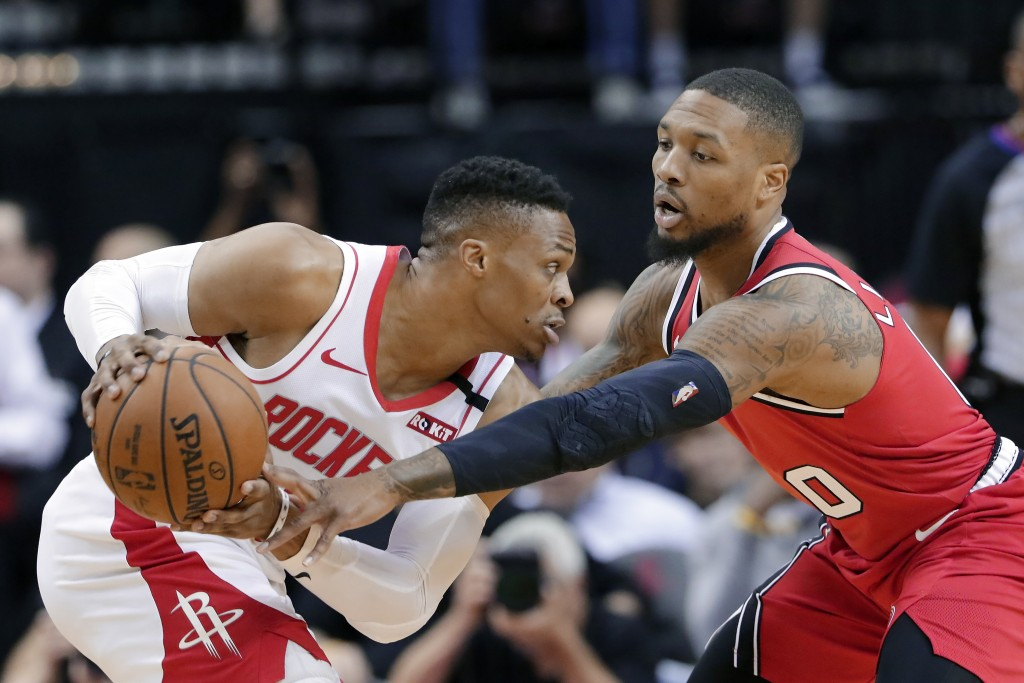 Houston Rockets guard Russell Westbrook (0) looks for a shot as Portland Trail Blazers guard Damian Lillard (0) reaches in during the first half of an...