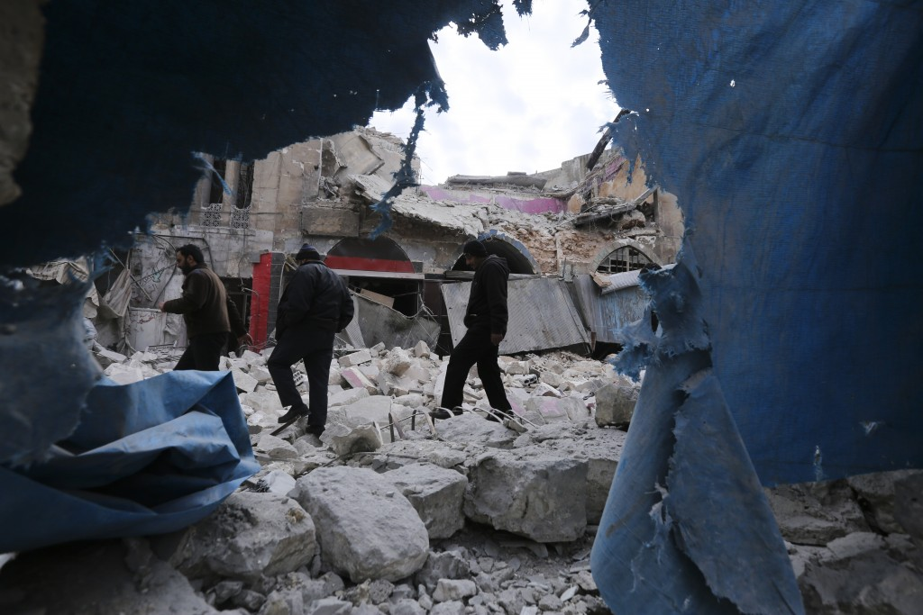 People walk past destruction by the government airstrikes in the town of Ariha, in Idlib province, Syria, Wednesday, Jan. 15, 2020. Syrian government ...
