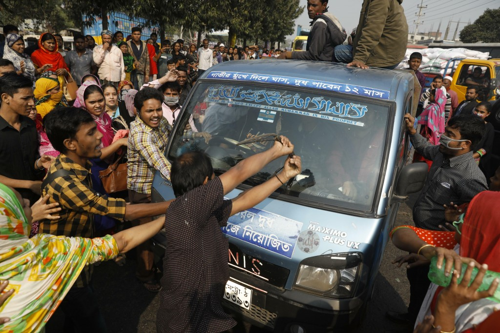 FILE - In this Wednesday, Jan. 9, 2019, file photo, Bangladeshi garment workers vandalize a vehicle during a protest demanding better wages in Savar, ...