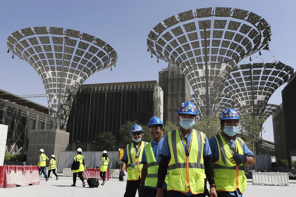 FILE - In this Oct. 8, 2019, file photo, technicians walk at the three thematic districts at the under construction site of the Expo 2020 in Dubai, Un...