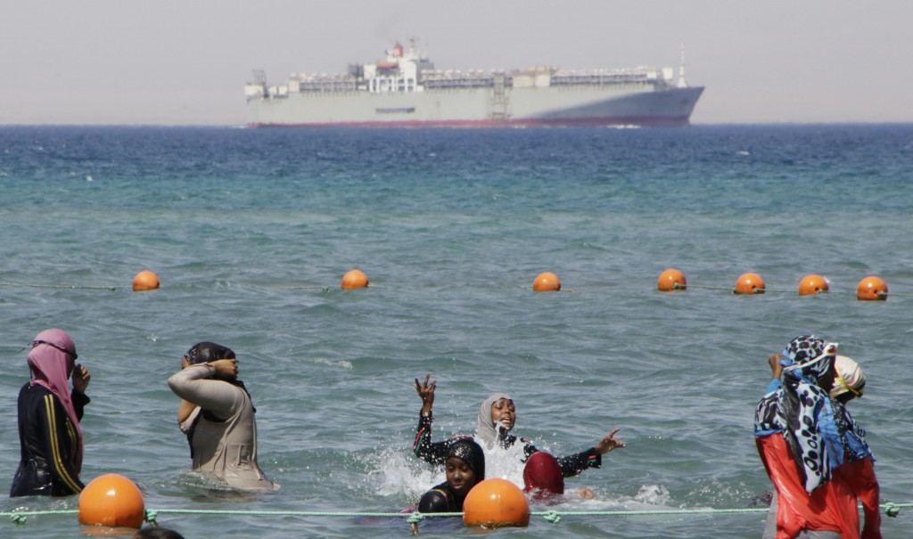 FILE - In this Sunday, Aug. 9, 2015 file photo, a ship crosses the Gulf of Suez towards the Red Sea as holiday-makers swim in Suez, 127 kilometers (79...