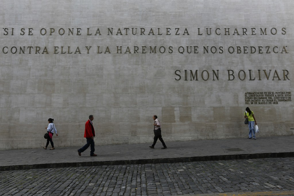 "People walk past a quote by Simon Bolivar that reads in Spanish: ""If nature opposes, we will fight against her and make her obey us,"" near the Nationa..."