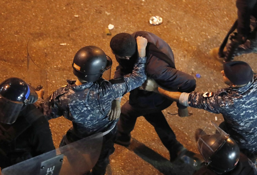 Riot police arrest an anti-government protester who was protesting outside a police headquarters demanding the release of those taken into custody the...