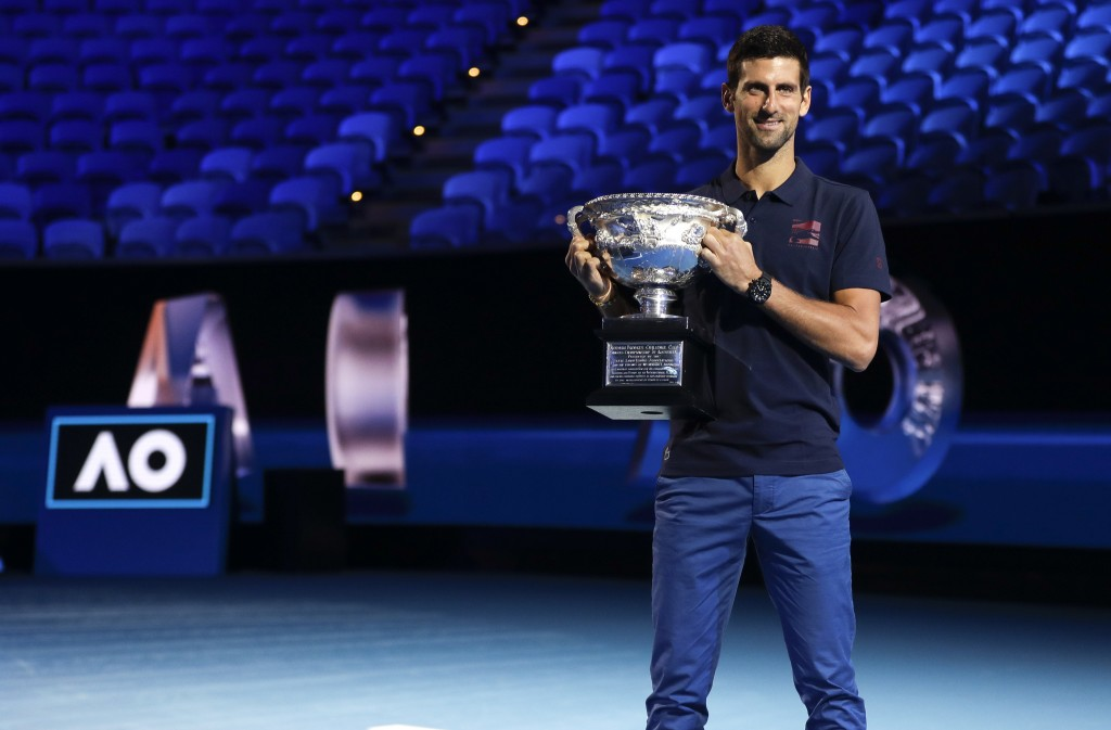 Defending men's singles champion Serbia's Novak Djokovic holds the Norman Brookes Challenge Cup during the official draw ceremony on Margaret Court Ar...