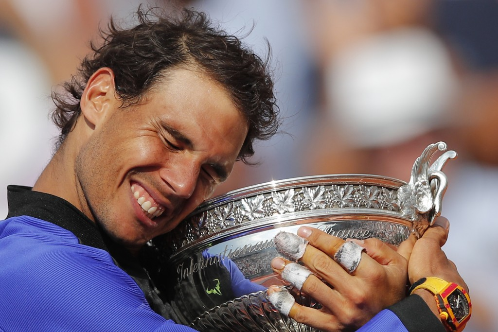FILE - In this June 11, 2017, file photo, Spain's Rafael Nadal holds the trophy as he celebrates winning his tenth French Open title, against Switzerl...
