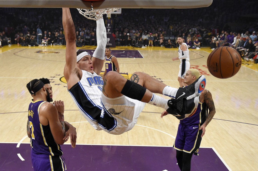 Orlando Magic forward Aaron Gordon, center, dunks as Los Angeles Lakers center JaVale McGee, left, and forward Kyle Kuzma, right, stand by during the ...