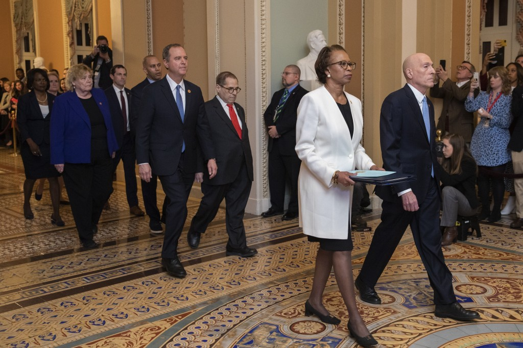 House Sergeant at Arms Paul Irving and Clerk of the House Cheryl Johnson carry the articles of impeachment against President Donald Trump to Secretary...