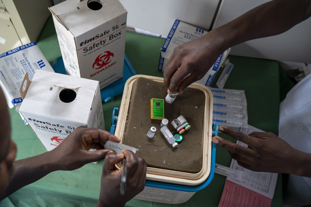 In this photo taken Tuesday, Dec. 10, 2019, health officials prepare to vaccine residents of the Malawi village of Migowi, where young children become...