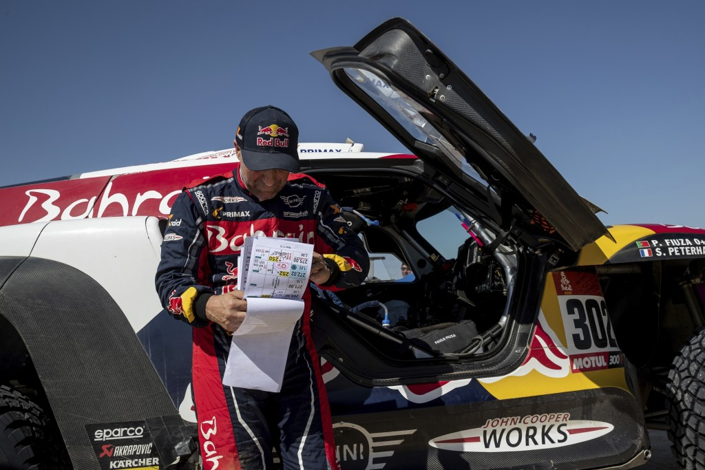 Driver Stephane Peterhansel, of France, checks the road book during stage eleven of the Dakar Rally between Shubaytah and Haradth, Saudi Arabia, Thurs...