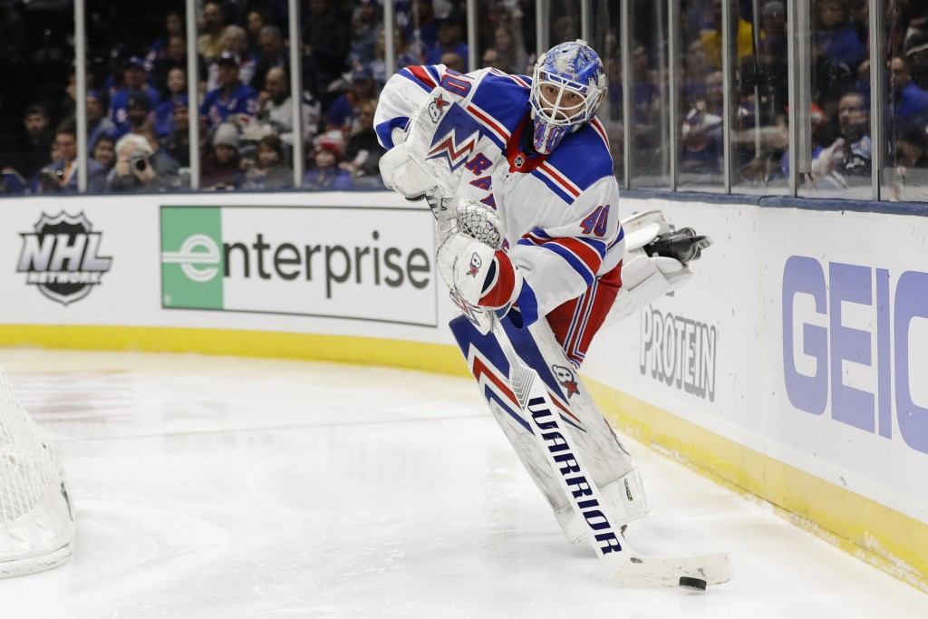 New York Rangers goaltender Alexandar Georgiev (40) passes to a teammate during the second period of an NHL hockey game against the New York Islanders...