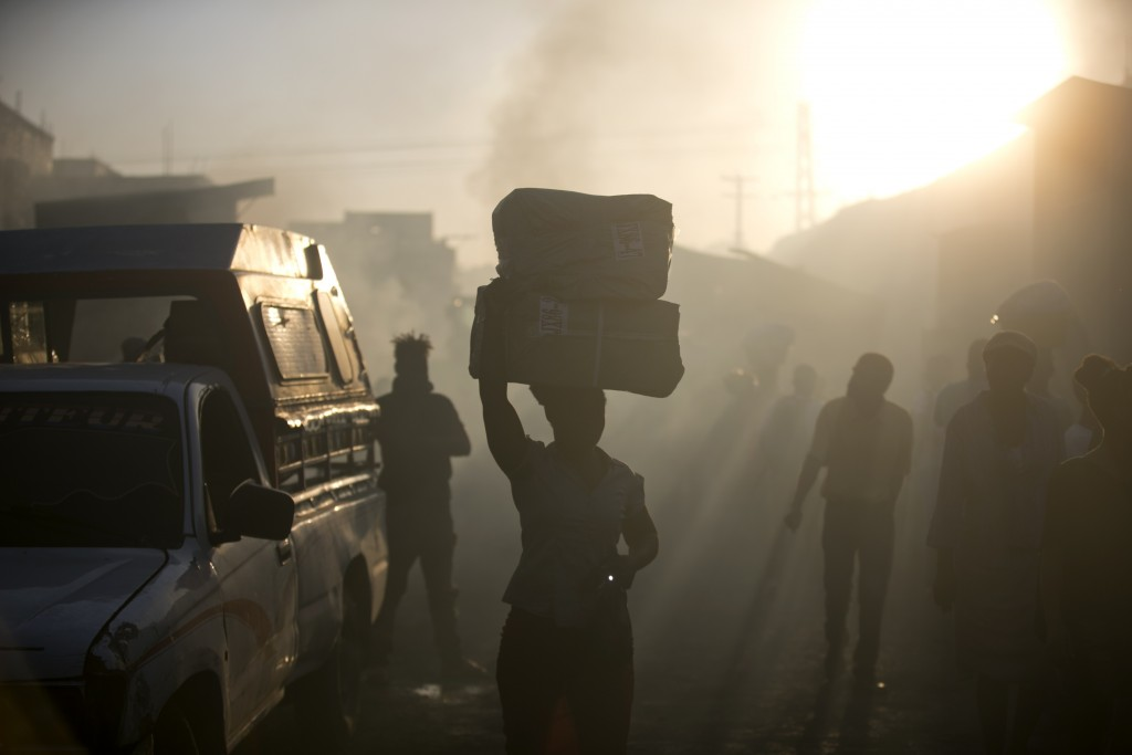 A vendor carries away her salvaged merchandise from the burned ruins of the Guerite Market that was engulfed in flames in Port-au-Prince, Haiti, early...