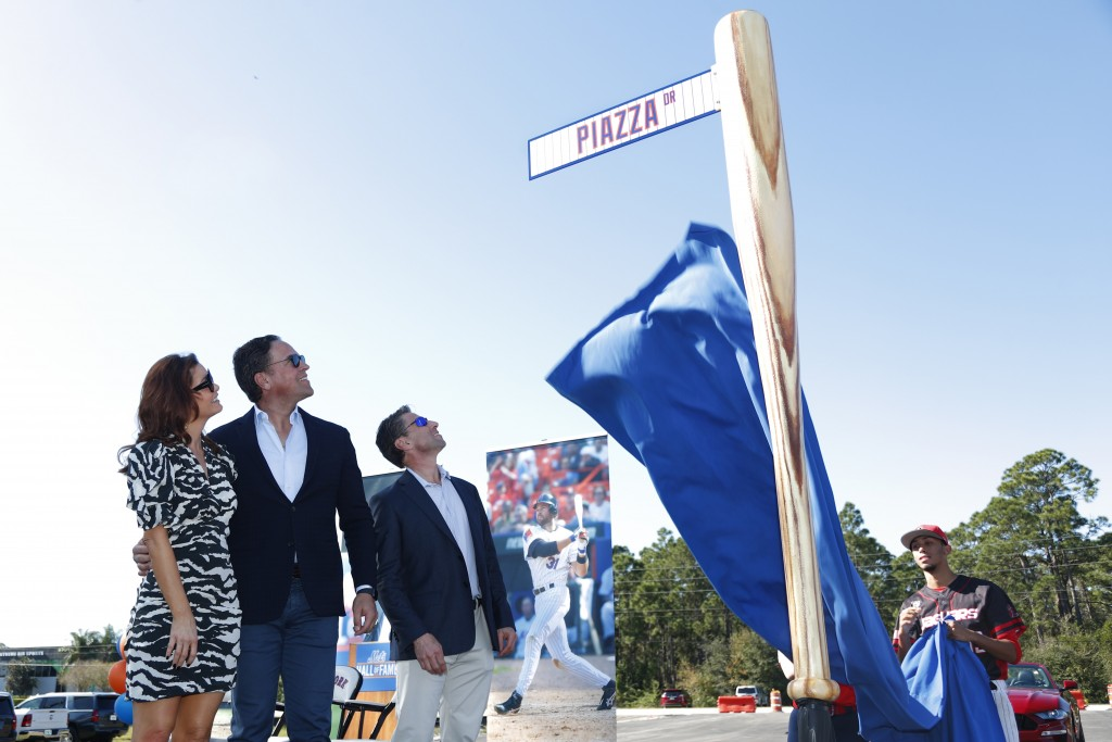 Former New York Mets catcher Mike Piazza, center left, his wife Alicia, left, and Mets COO Jeff Wilpon watch as newly named Piazza Dr., is unveiled du...