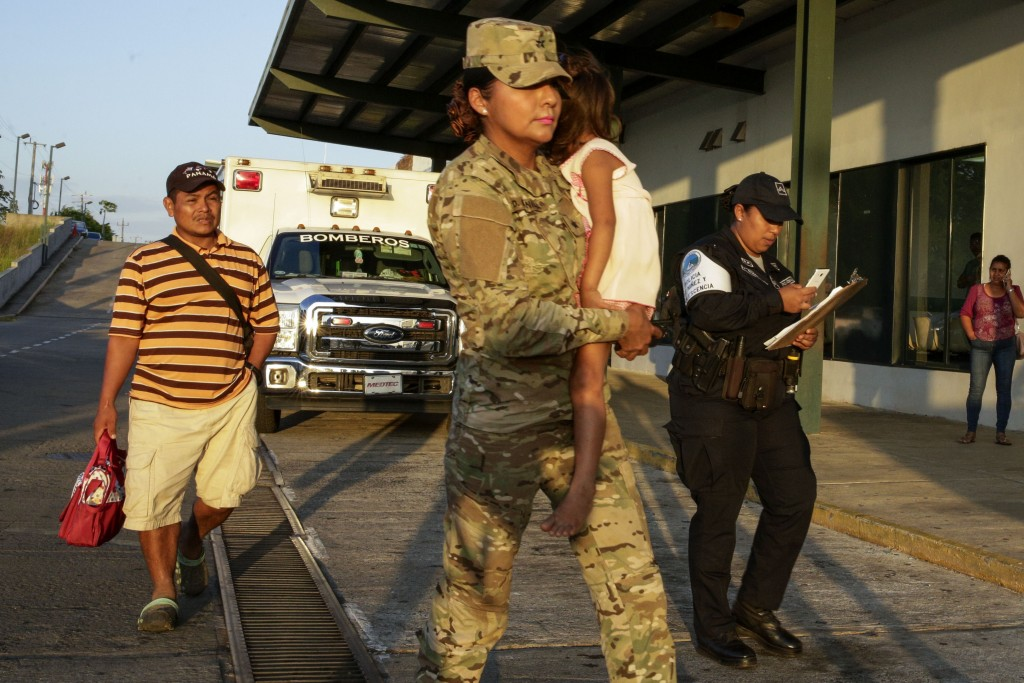 Jose Gonzalez, left, follows his 5-year-old daughter, carried by a police officer, as they leave a hospital in Santiago, Panama, Thursday, Jan. 16, 20...