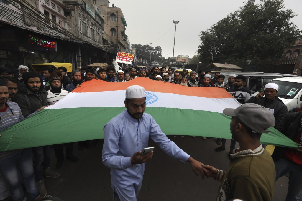 Indian Muslims carry a giant Indian flag during a protest against a new Citizenship law, after Friday prayers in New Delhi, India, Friday, Jan. 17, 20...