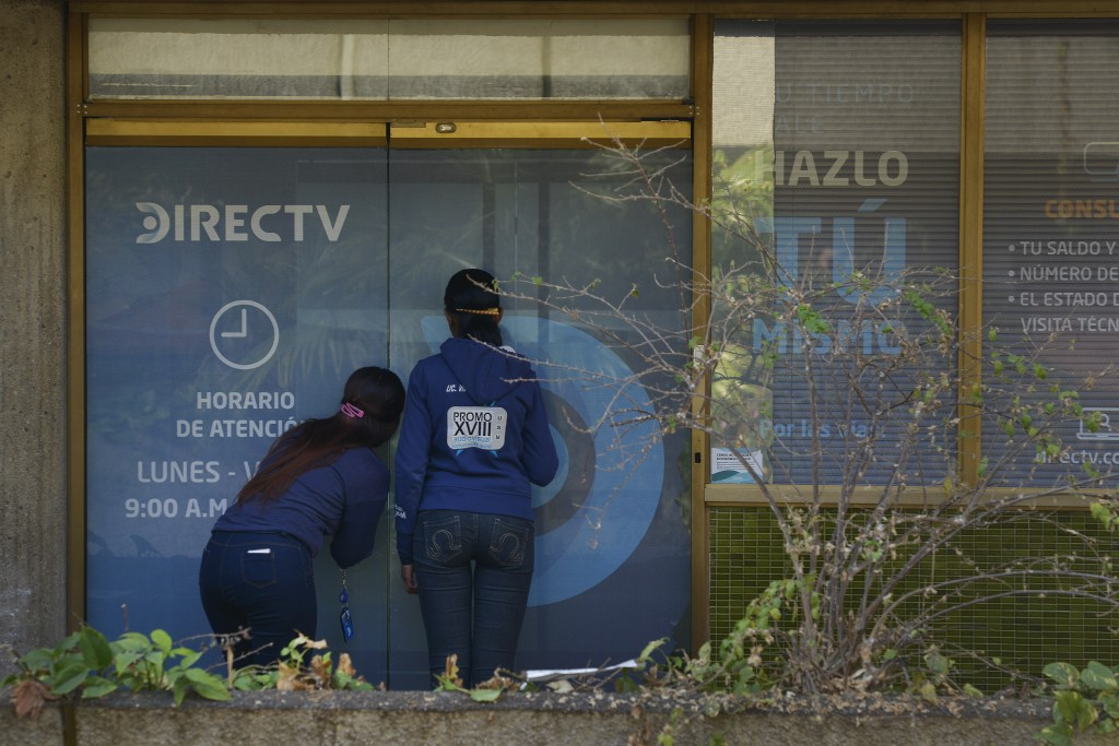 In this Jan. 9, 2020 photo, clients wait to enter the DirecTV headquarters in Caracas, Venezuela. Venezuelan President Maduro's opponents want AT&T's ...