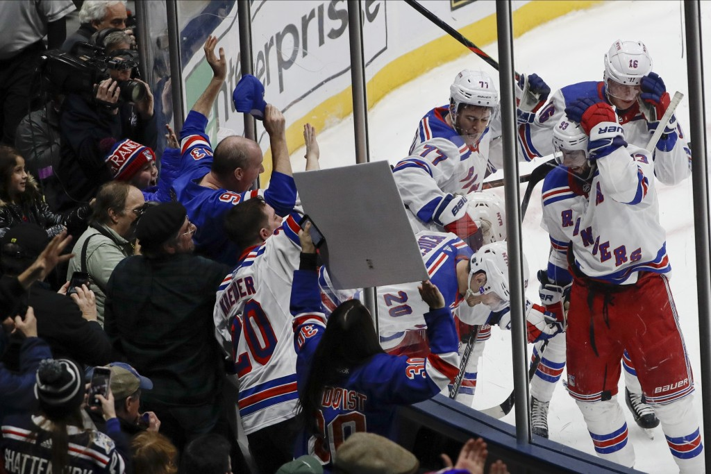 Fans watch as New York Rangers' Chris Kreider (20) celebrates with teammates after scoring a goal during the third period of an NHL hockey game agains...