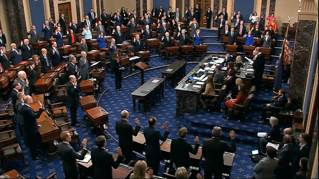 In this image from video, presiding officer Supreme Court Chief Justice John Roberts swears in members of the Senate for the impeachment trial against...