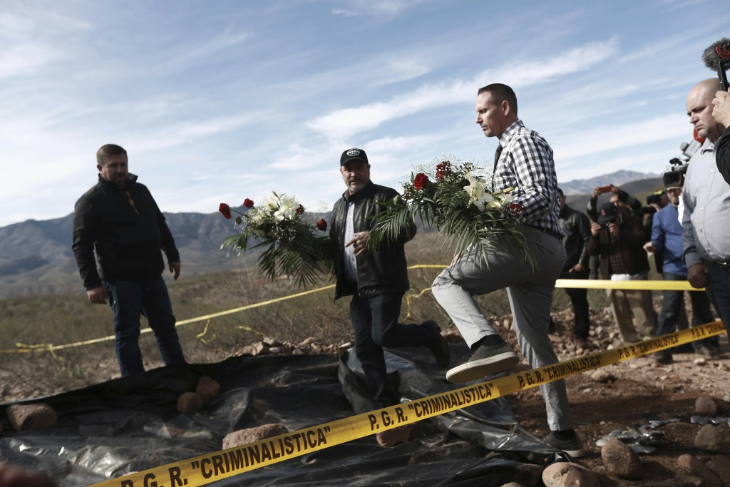 Bryan Lebaron, second from right, and relatives place flowers where one of the cars belonging to the extended LeBaron family was ambushed by gunmen la...