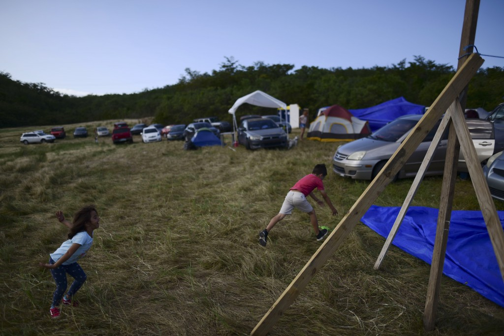 In this Friday, Jan. 10 photo, children play on a hay farm where residents from the Indios neighborhood of Guayanilla, Puerto Rico, have set up shelte...