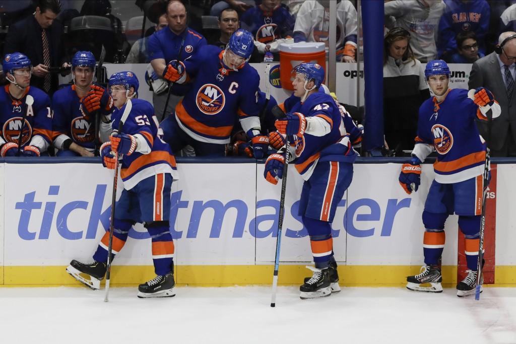 New York Islanders center Casey Cizikas (53) and Leo Komarov (47) react with teammates after New York Rangers' Chris Kreider scored a goal during the ...