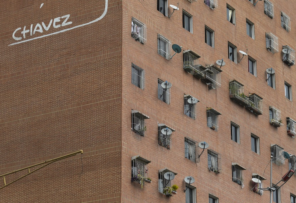 In this Jan. 9, 2020 photo, DirectTV dish antennas cover the exterior wall of an apartment building featuring the last name of late President Hugo Cha...