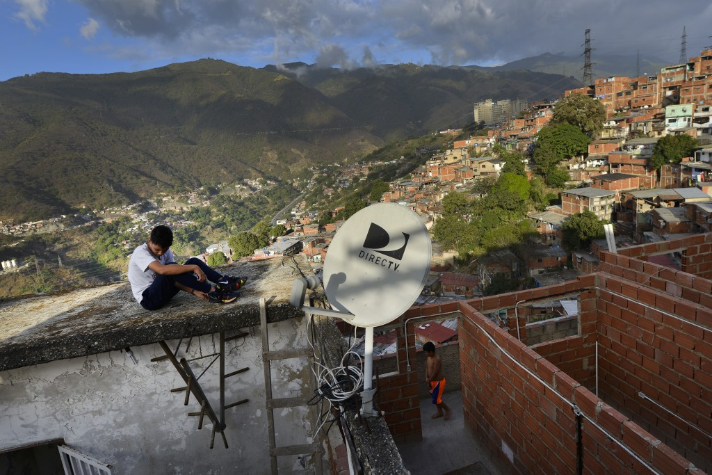 A DirectTV dish stands on home in the Catia neighborhood of Caracas, Venezuela, Thursday, Jan. 9, 2020. Venezuelan President Maduro's opponents want A...