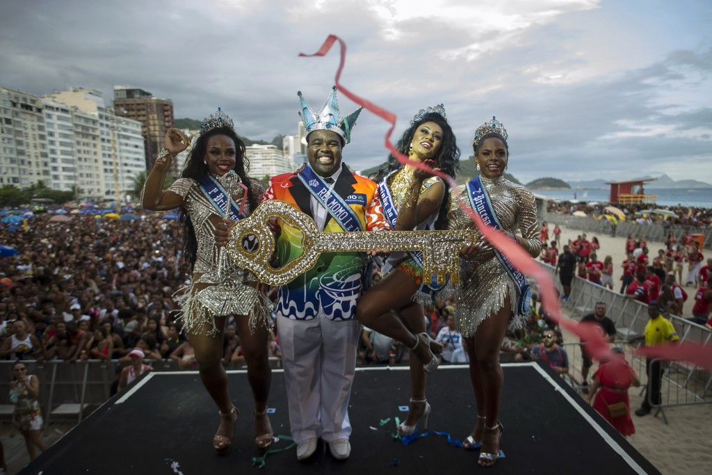 Carnival King Momo, Djeferson Mendes da Silva, second from left, holds the key to the city at a ceremony marking the official start of Carnival on Cop...