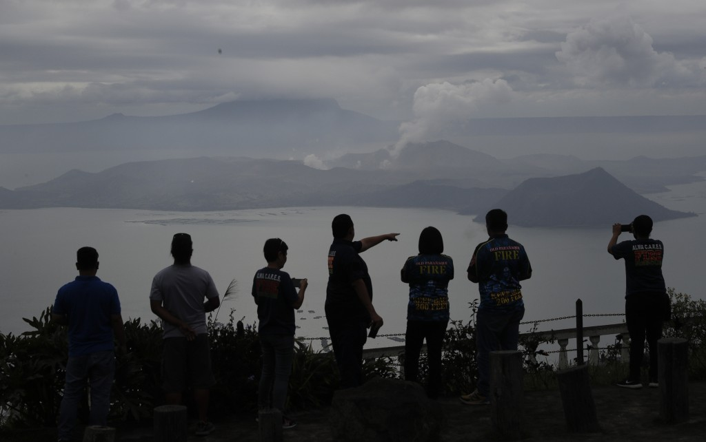 People look at Taal volcano in Tagaytay, Cavite province, southern Philippines on Friday Jan. 17, 2020. Taal volcano remains life-threatening despite ...