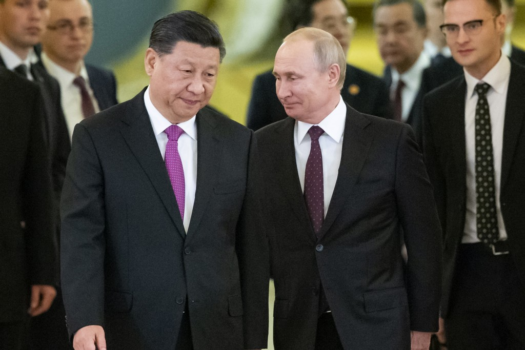FILE - In this June 5, 2019, file photo, Russian President Vladimir Putin, center right, and Chinese President Xi Jinping, center left, enter a hall f...
