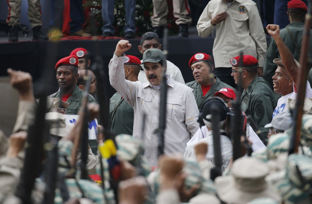 FILE - In this  April 13, 2019 file photo, Venezuela's President Nicolas Maduro gestures to members of the Bolivarian Militia during their 10th annive...