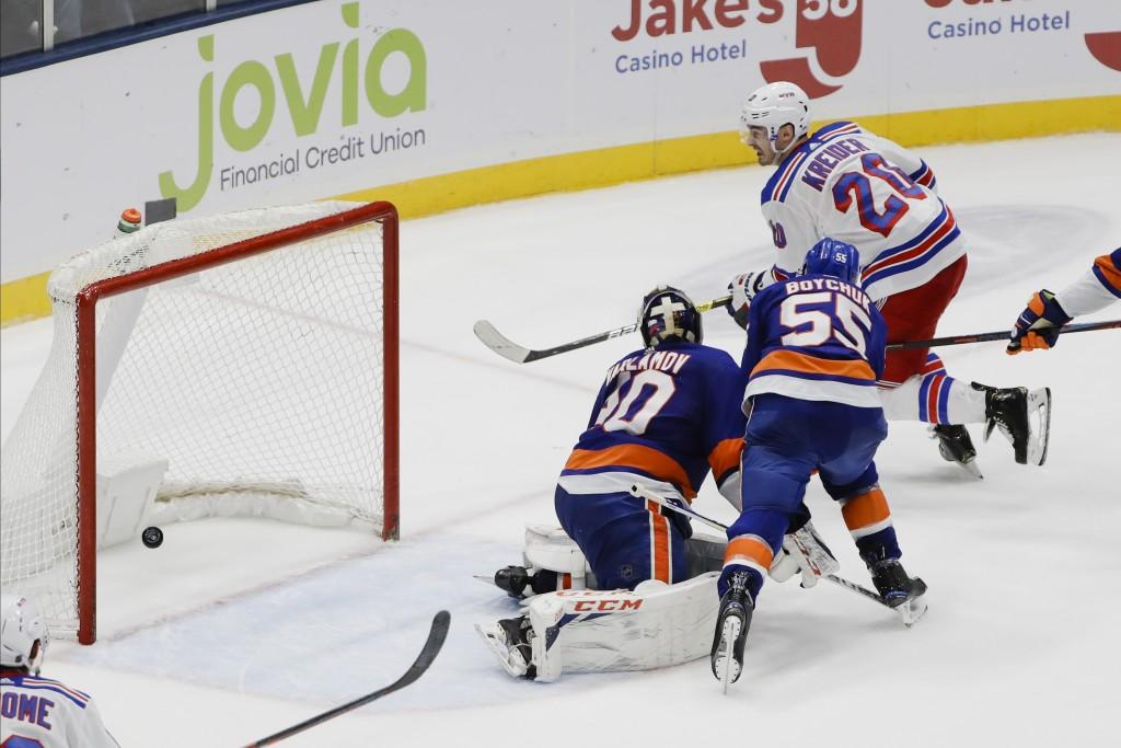 New York Rangers' Chris Kreider (20) shoots the puck past New York Islanders goaltender Semyon Varlamov (40) and Johnny Boychuk (55) for the game winn...