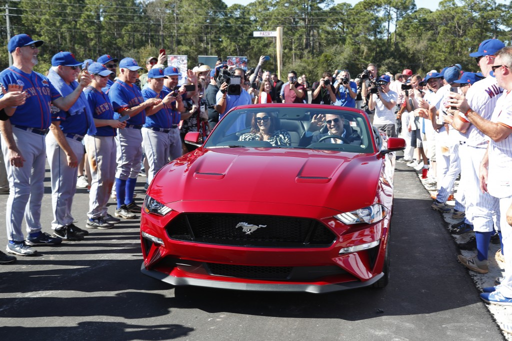 Former New York Mets catcher Mike Piazza and his wife Alicia wave as they drive down newly named Piazza Dr., after a ceremony in front of the Mets spr...