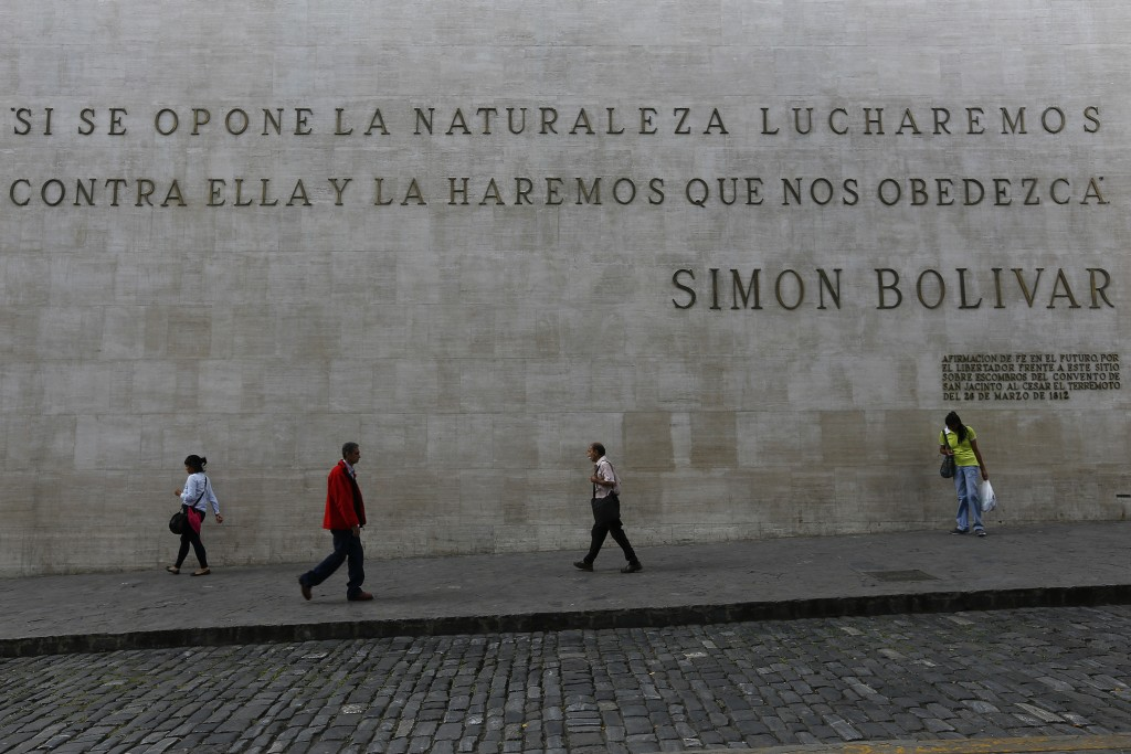 """People walk past a quote by Simon Bolivar that reads in Spanish: """"If nature opposes, we will fight against her and make her obey us,"""" near the Nationa..."""