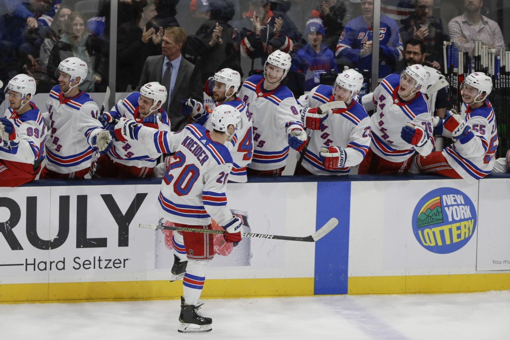 New York Rangers' Chris Kreider (20) celebrates with teammates after scoring a goal during the third period of an NHL hockey game against the New York...