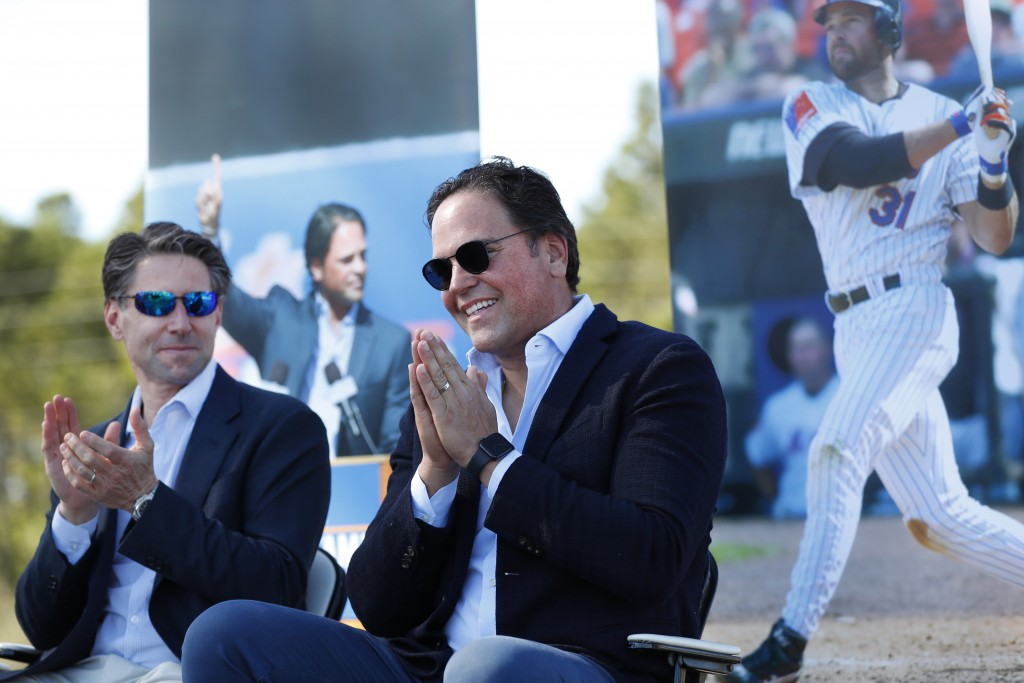 Former New York Mets catcher Mike Piazza, right, acknowledges the crowd as Mets COO Jeff Wilpon, left, claps during a ceremony to name a street Piazza...