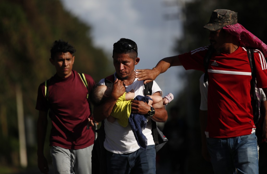 Honduran migrant Selvin Hernandez carries Mayra Irene, the baby daughter of another migrant, as another man tries to shade her with his hand amid a gr...