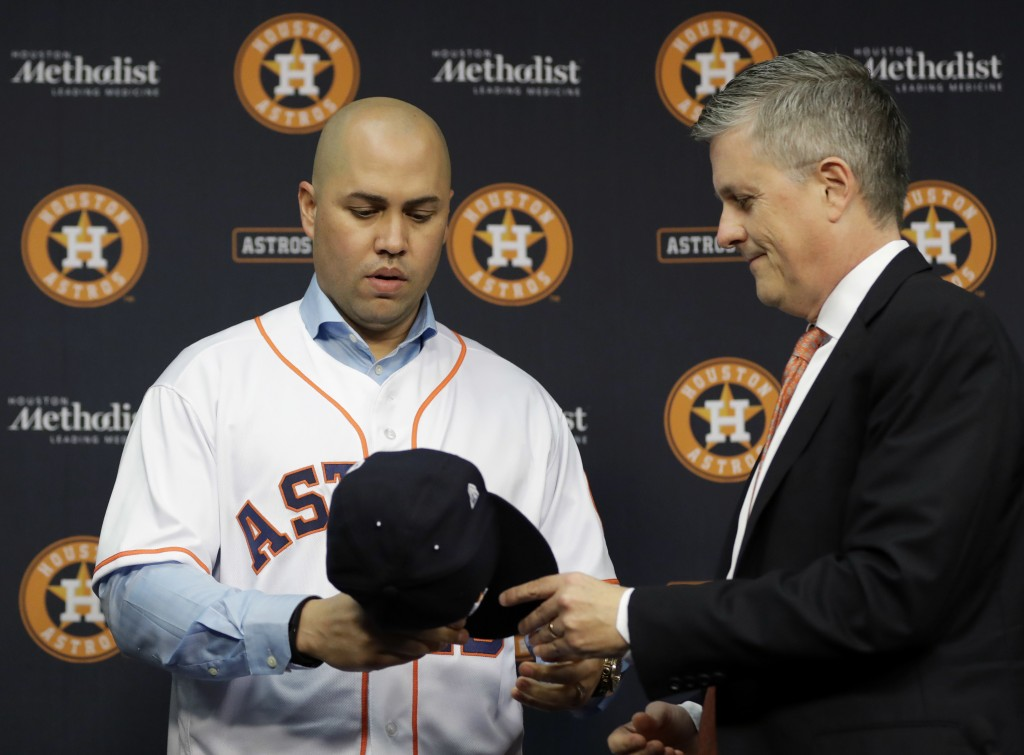 FILE - In this Dec. 5, 2016, file photo, Houston Astros general manager Jeff Luhnow, right, hands outfielder Carlos Beltran a cap during a news confer...