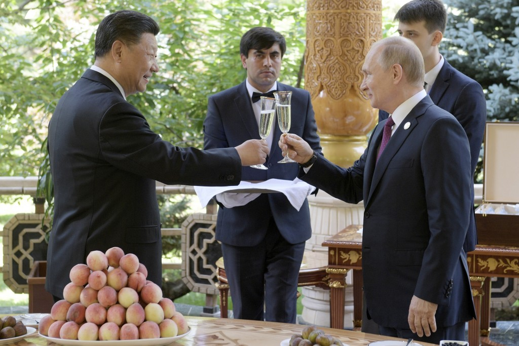 FILE - In this June 14, 2019, file photo, Russian President Vladimir Putin, right, toasts with Chinese President Xi Jinping prior to the Conference on...