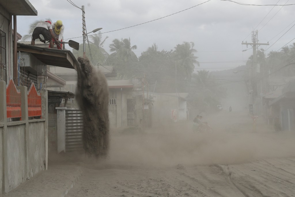 Residents shovel volcanic ash from the roof of their homes at a village near Taal volcano where people have evacuated to safer grounds in Agoncillo, B...